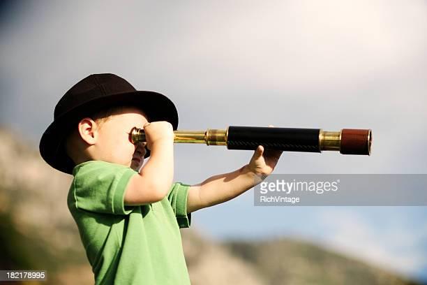 Jeune garçon regardant à travers un télescope