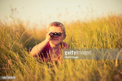 Young Boy Looking Through Binoculars Hiding in Grass