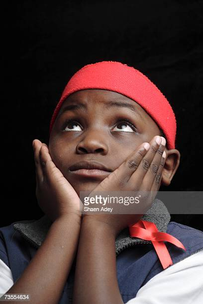 Young Boy Looking Up with His Hands On His Cheeks