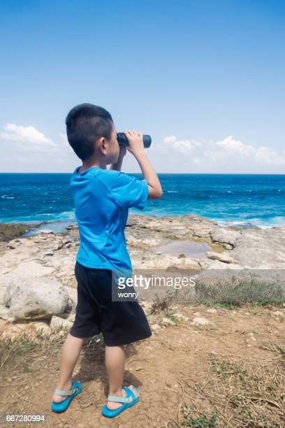 Young boy looking with binoculars on cliff