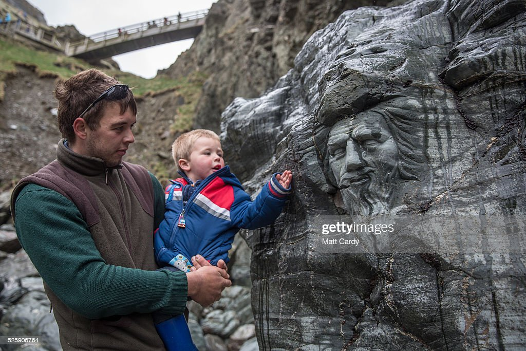A young boy looks at a carving of Merlin at Tintagel Castle in Tintagel on April 28, 2016 in Cornwall, England. The English Heritage managed site and the nearby town have long been associated with the legend of King Arthur and continue to attract large visitor numbers. However, efforts by English Heritage to update the visitor experience with the Gallos sculpture, along with a rock carving of Merlin's face, which English Heritage say are inspired by the legend of King Arthur and Tintagel Castles royal past, have met with criticism from some Cornish nationalists and historians.