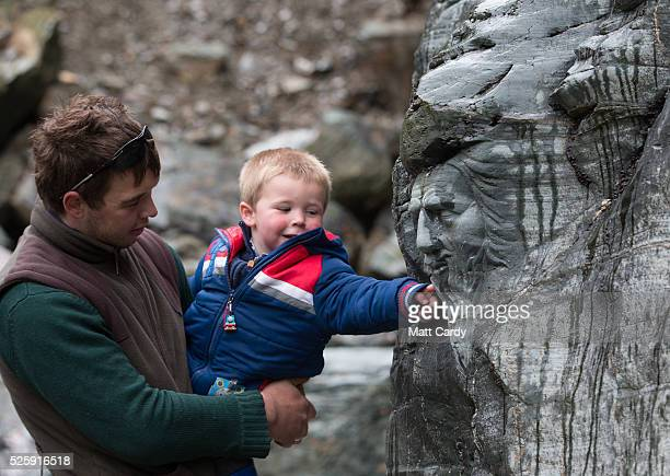 A young boy looks at a carving of Merlin at Tintagel Castle in Tintagel on April 28 2016 in Cornwall England The English Heritage managed site and...