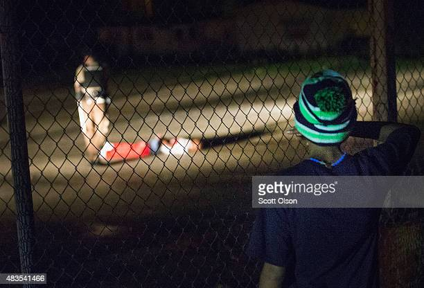 A young boy looks at a man with gunshot wounds lying in a parking lot after a shoot out with police along West Florissant Street during a...