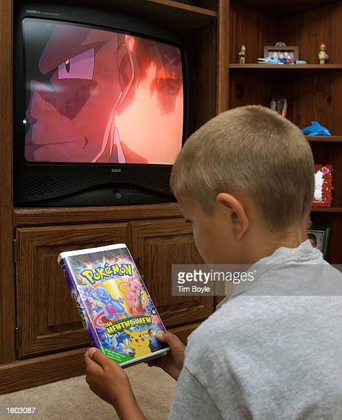 A young boy looks at a Pokemon video cassette box in his parent''s home July 20 2001 in Des Plaines IL home