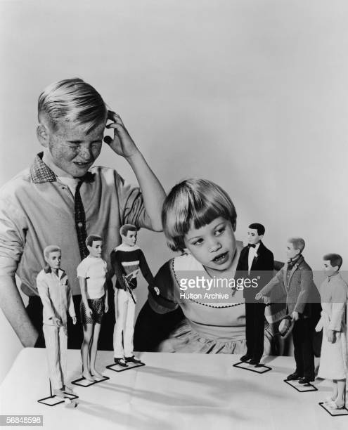 A young boy looks on and scratches his head in confusion as a younger girl inspects the new line of 'Ken' dolls from Mattel 1961 Ken whose last name...