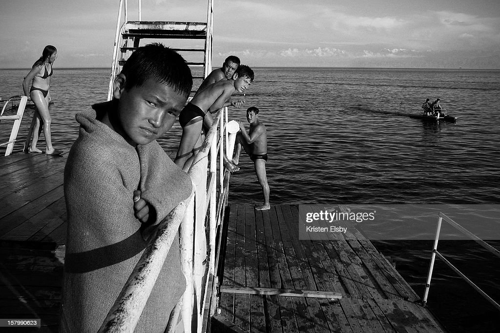 A young boy looks on as older boys entertain each other with spectacular dives off the pier of Lake Issyk-Kul, Kyrgyzstan, during a hot, summer afternoon.