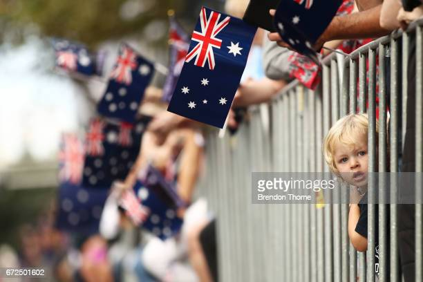 A young boy looks on as war veterans make their way down Elizabeth Street during the ANZAC Day parade on April 25 2017 in Sydney Australia...