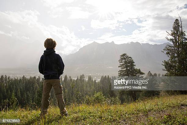 Young boy looks out to mtns during rainstorm
