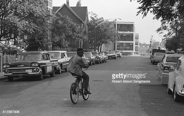 A young boy looks over his shoulder as he bicycles along South Langley Street in the South Side neighborhood Chicago Illinois 1969