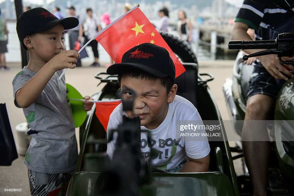 A young boy looks through the iron sight of a gun during the open day of the Chinese People's Liberation Army (PLA) Navy Base at Stonecutter Island in Hong Kong on July 1, 2016, to mark the 19th anniversary of the Hong Kong handover to China . / AFP / Anthony Wallace