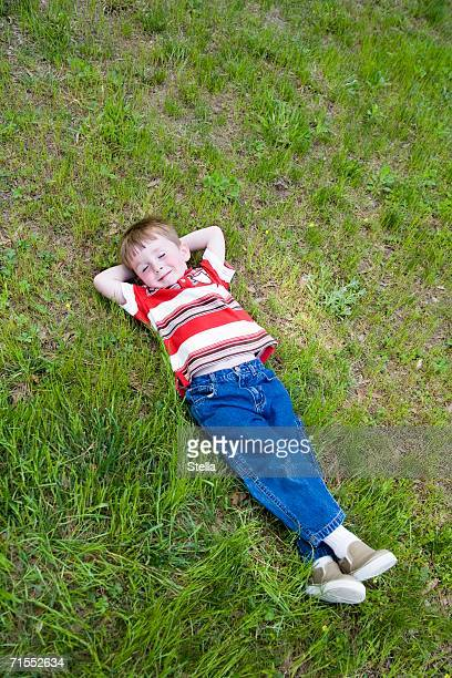 Young boy lying down on grass with eyes closed and hands behind head