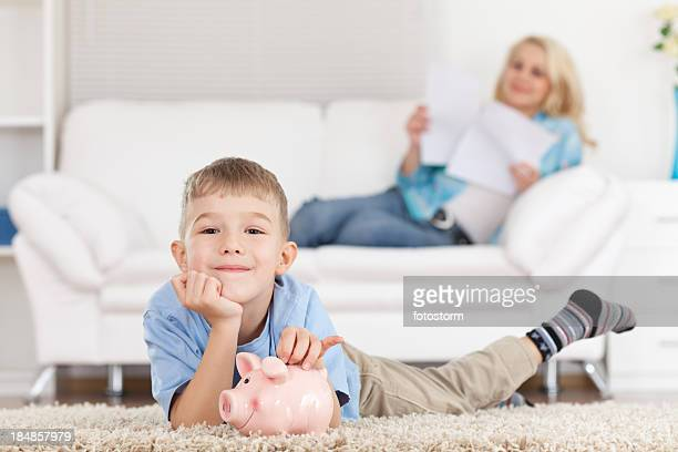 Young boy lying on a carpet with a piggy bank