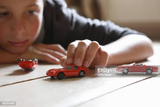 young boy lying on floor playing with toy cars