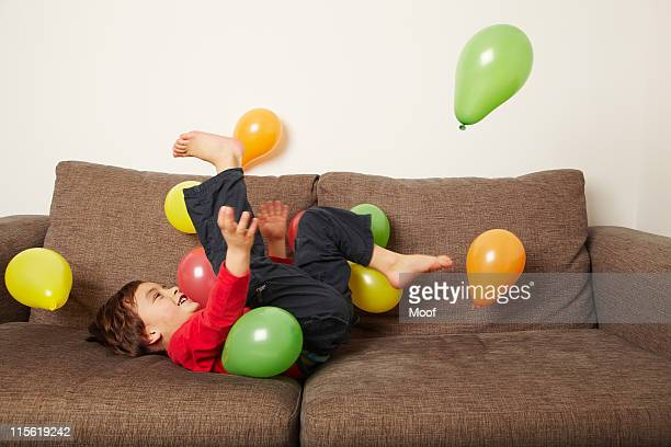 Young boy lying on sofa kicking balloons