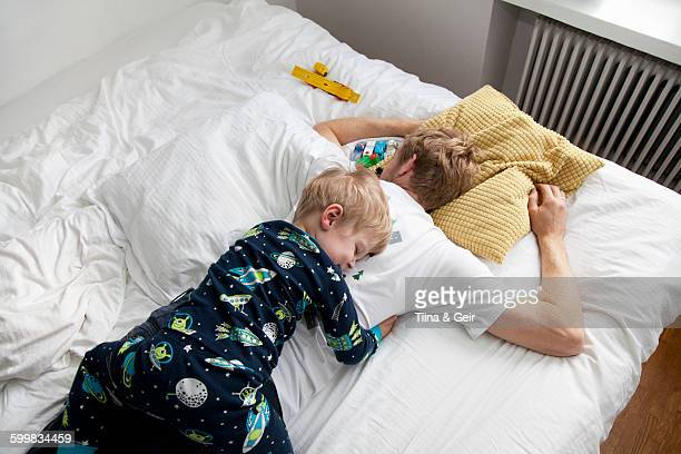 Young boy lying on top of father n bed