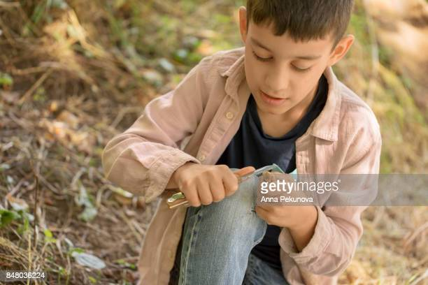 Young boy making arrow from a stick