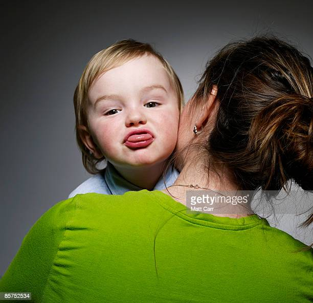 Young Boy making faces on mom's shoulder