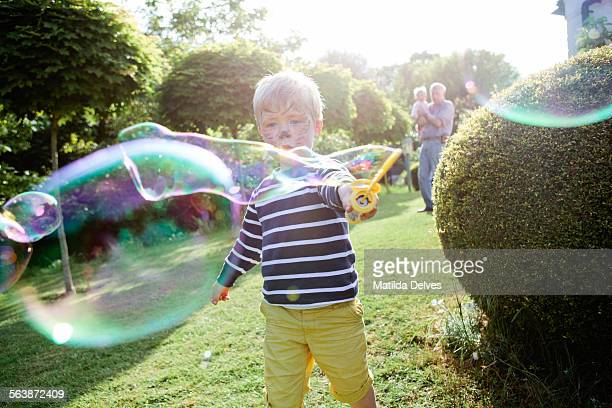 Young boy making giant soap bubbles