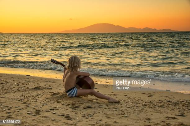Young boy making some music at the beach, Zakynthos,  Ionian Islands, Greece
