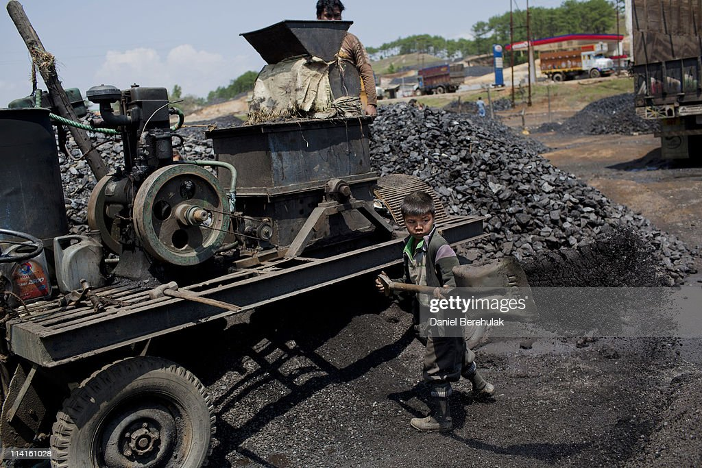 A young boy named Fight, believed to be 8 years old, shovels coal at a depot on April 15, 2011 near Lad Rymbai, in the district of Jaintia Hills, India. Local schools in the area, providing free tuition, find it difficult to convince parents of the benefits of education, as children are seen as sources of income. The lure of the mines is stronger than that of the classroom. The Jaintia hills, located in India's far North East state of Meghalaya, miners descend to great depths on slippery, rickety wooden ladders. Children and adults squeeze into rat hole like tunnels in thousands of privately owned and unregulated mines, extracting coal with their hands or primitive tools and no safety equipment. Workers can earn as much as 150 USD per week or 30,000 Rupees per month, significantly higher than the national average of 15 USD per day. After traversing treacherous mountain roads, the coal is delivered to neighbouring Bangladesh and to Assam from where it is distributed all over India, to be used primarily for power generation and as a source of fuel in cement plants. Many workers leave homes in neighbouring states, and countries, like Bangladesh and Nepal, hoping to escape poverty and improve their quality of life. Some send money back to loved ones at home, whilst many others squander their earnings on alcohol, drugs and prostitution in the dusty, coal mining towns like Lad Rymbai. Some of the labor is forced, and an Indian NGO group, Impulse, estimates that 5,000 privately-owned coal mines in Jaintia Hills employed some 70,000 child miners. The government of Meghalaya refuted this figure, claiming that the mines had only 222 minor workers. Despite the ever present dangers and hardships, children, migrants and locals flock to the mines hoping to strike it rich in India's wild east.