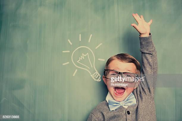 Jeune garçon de Nerd a une idée dans une salle de classe