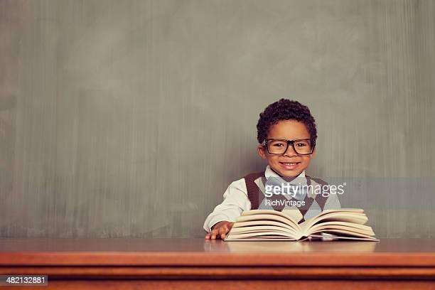 Giovane ragazzo Nerd lettura alla scrivania in aula