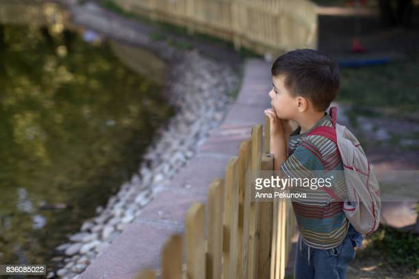 Young boy next to a wooden fence