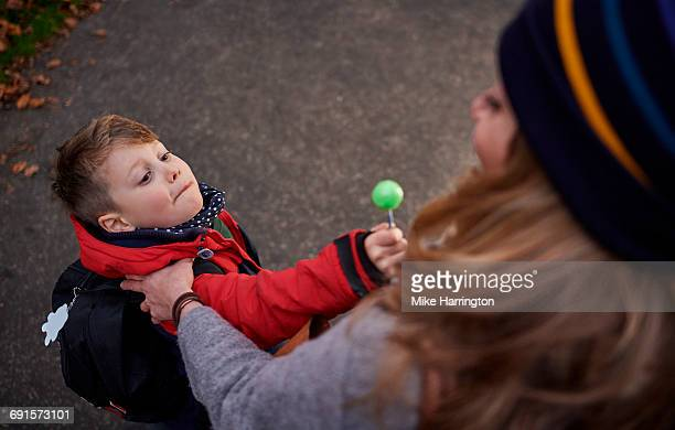 Young boy offering his mum a lollypop