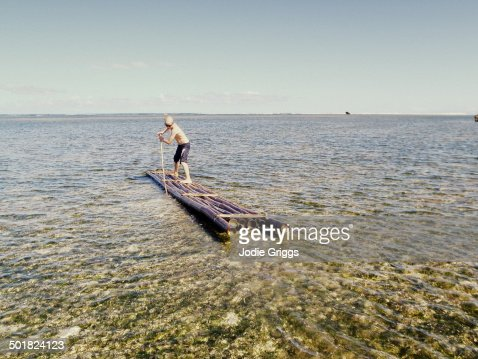 Young boy on a bamboo raft on tropical reef