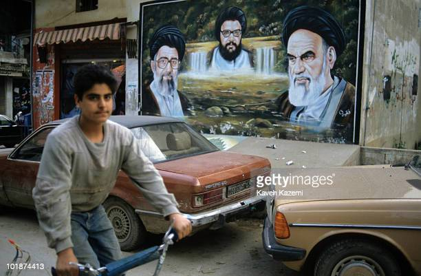 A young boy on a bicycle passes by a mural in Beirut painted with portraits of Ayatollah Khomeini and Ayatollah Ali Khamenei who are present and past...