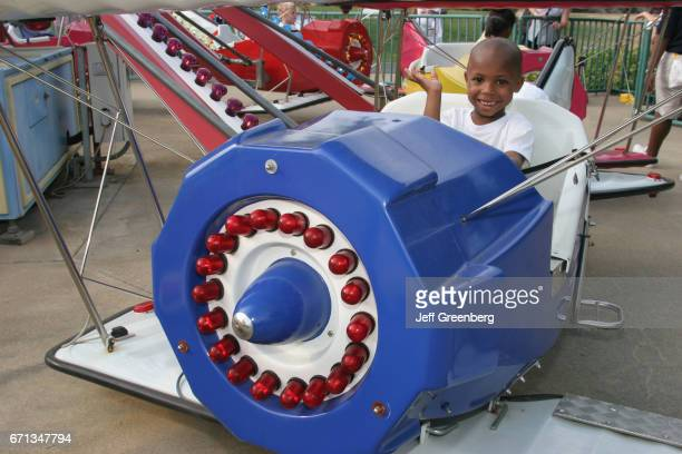 A young boy on an airplane kiddie ride at VisionLand Magic Adventure Theme Park