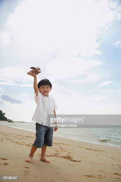young boy on beach flying wooden airplane