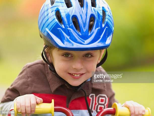 Young boy on bike, wearing helmet
