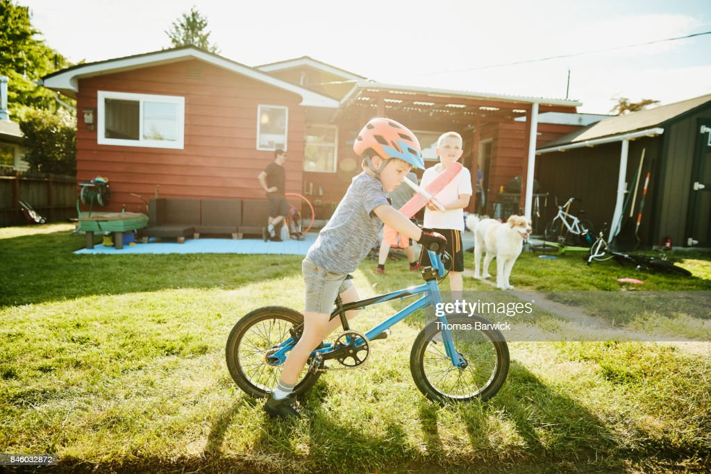 Young boy on BMX bike in backyard on summer afternoon : Stock Photo