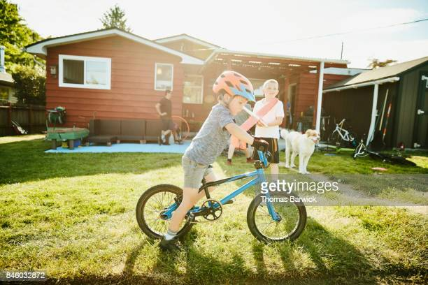 Young boy on BMX bike in backyard on summer afternoon