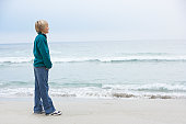 Young Boy On Holiday Standing On Winter Beach Looking Out To Sea