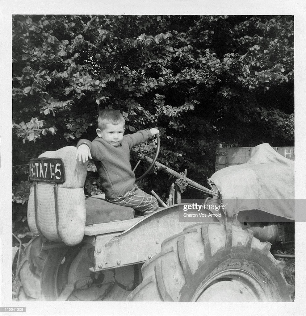 Young boy on old tractor : Stock Photo
