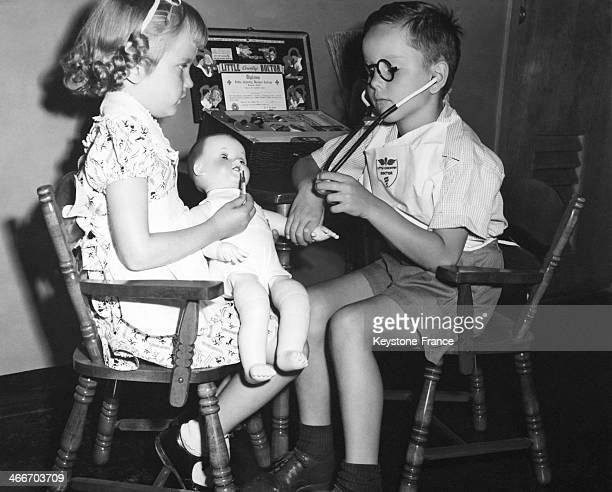 Young boy on right looking quite professional as the doctor with this Little Doctor Kit while young girl on left is the nurse and takes the doll's...