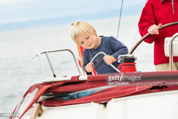 Young boy on sailing boat with great grandfather, mid section, Geneva, Switzerland, Europe
