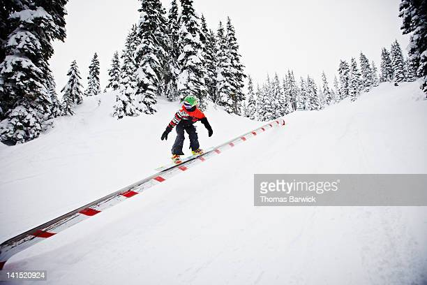 Young boy on snowboard riding rail at resort