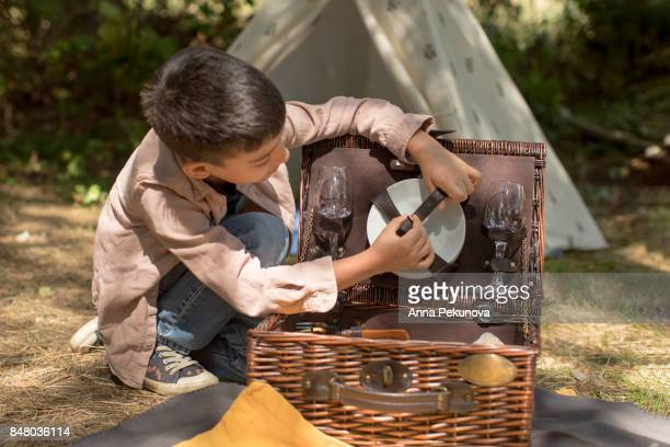Young boy opening picnic basket