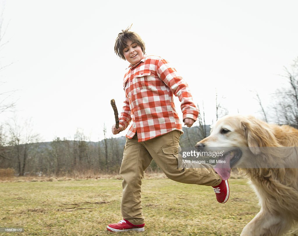 A young boy outdoors on a winter day, holding a stick and running with a golden retriever dog.  : Stock Photo