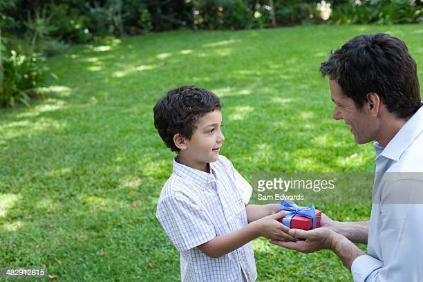 Young boy outdoors smiling and giving man gift