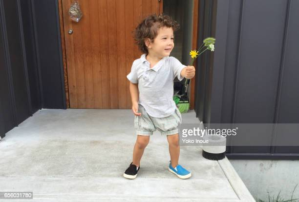 Young boy outside house with flowers