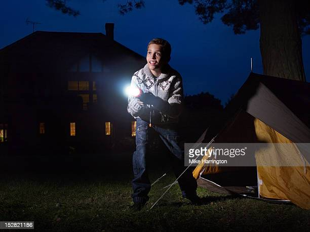 Young boy outside tent shining torch into distance