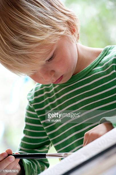 Young boy painting, low angle view
