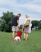 Young boy & parents outdoors.