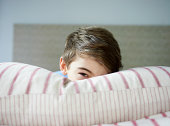 young boy peeking over pillow in bed
