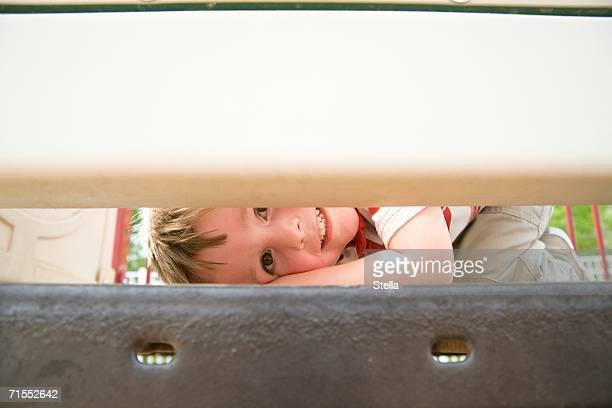 Young boy peeking through play equipment