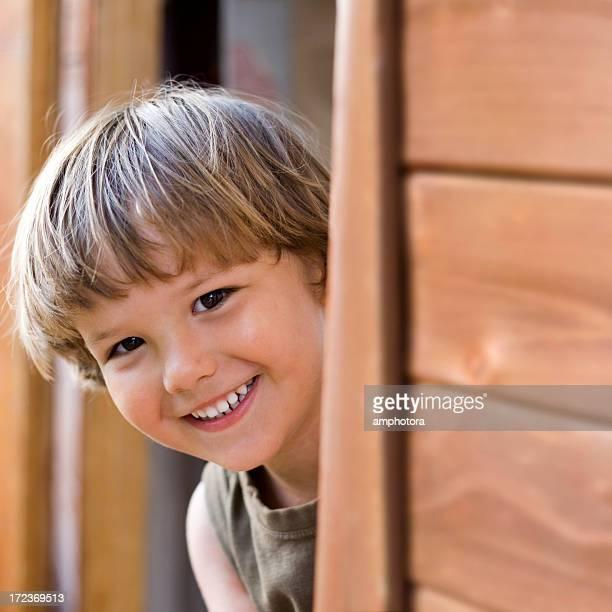 Young boy peering through a wooden doorway